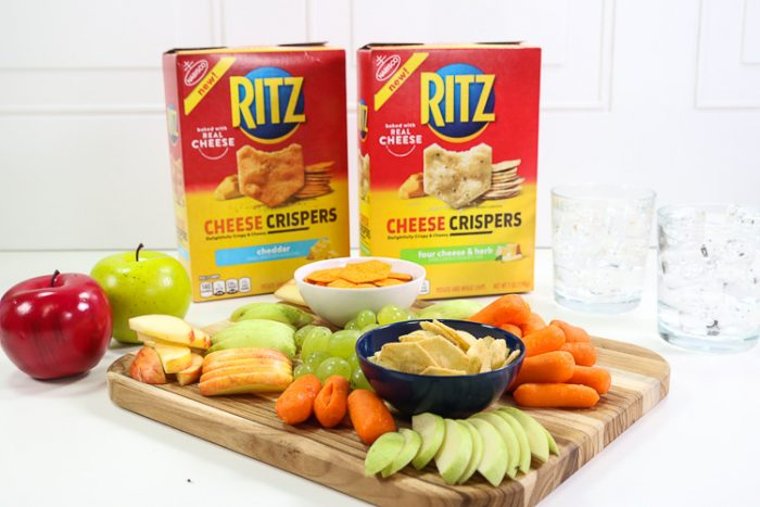 Overhead shot of board filled with fruit, veggies and Ritz Cheese Crispers with waters and horizontal