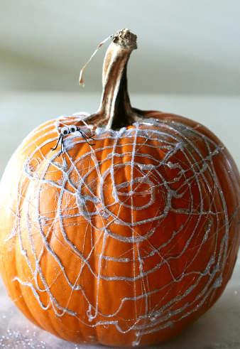 A pumpkin with hot glue and glitter spiderwebs