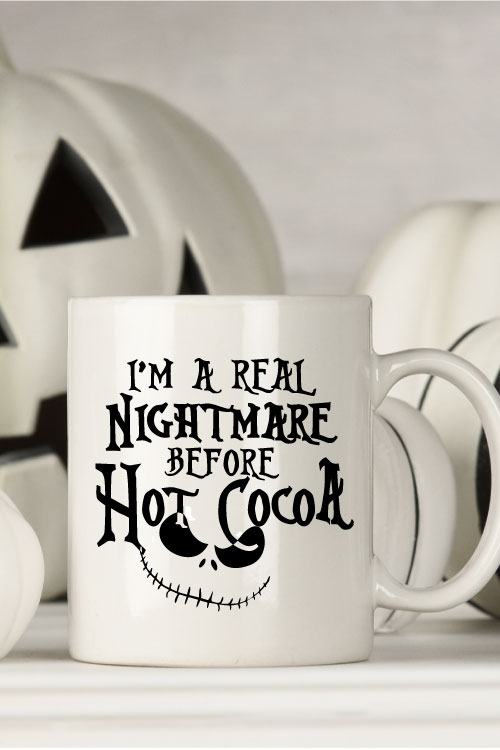 """White mug with black and white halloween decor behind. Mug Reads"""" I'm a Real Nightmare Before Hot Cocoa"""""""