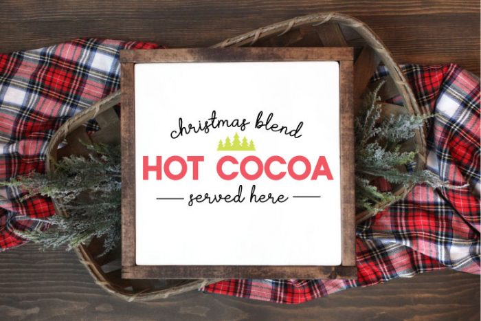 "Square sign with white background and wooden frame laying one a basket of evergreens snips and a plaid fabric.  ""Christmas Blend Hot Cocoa Served here"" is applied in vinyl"