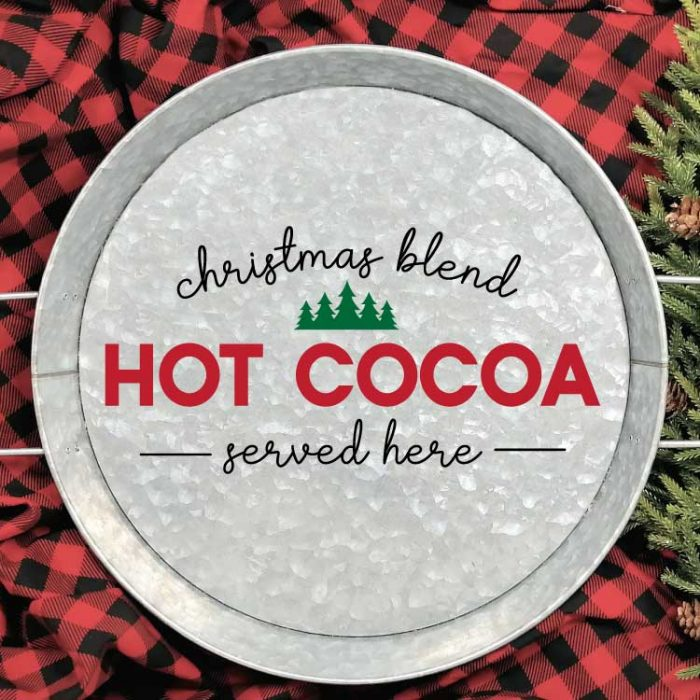 "Galvanized Serving Tray with ""Christmas Blend Hot Cocoa Served Here"" SVG applied in adhesive vinyl on a red and black buffalo check blanket with some greenery in square format"