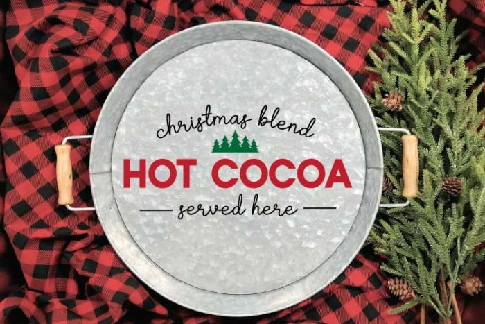 "Galvanized Serving Tray with ""Christmas Blend Hot Cocoa Served Here"" SVG applied in adhesive vinyl on a red and black buffalo check blanket with some greenery in horizontal format"