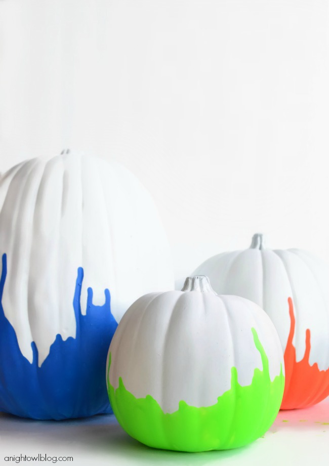 Pumpkins that have been painted white and dipped in neon paint