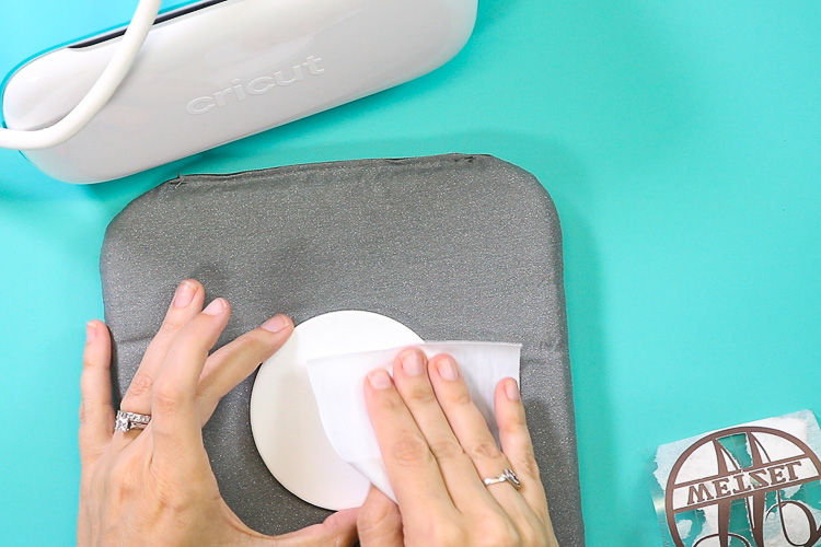 Using a lint free cloth to clean the surface of an infusible ink coaster