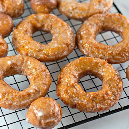 Pumpkin donuts and pumpkin donut holes on a black wire cooling rack