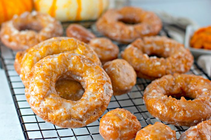 Close up of Pumpkin donuts on a black wire cooling rack
