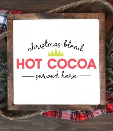 "Square sign with white background and wooden frame laying one a basket of evergreens snips and a plaid fabric. ""Christmas Blend Hot Cocoa Served here"" is applied in vinyl - vertical"