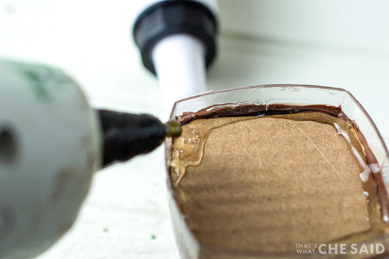 close up of hot glue gun gluing cardboard in place