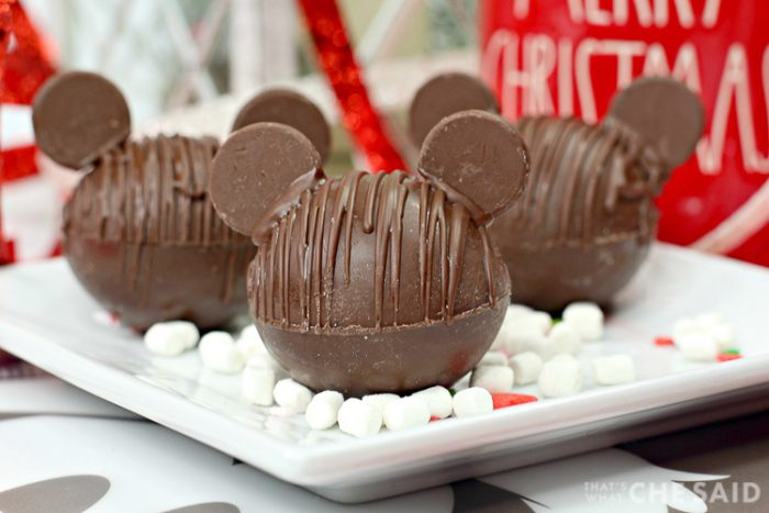 Three Chocolate Hot Chocolate Bomb with added chocolate wafers as ears to resemble Mickey Mouse with marshmallows and Christmas decor in background