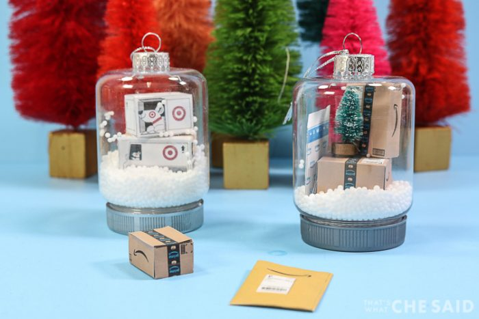 Two snow globe jar ornaments. One has miniature target boxes and one has miniature Amazon boxes and envelopes
