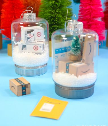 Two snow globe jar ornaments. One has miniature target boxes and one has miniature Amazon boxes and envelopes Vertical Orientation