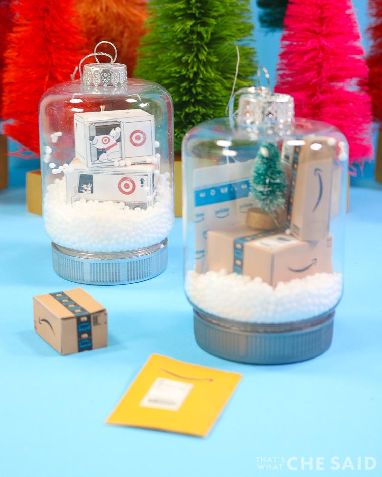 Two snow globe jar ornaments. One has miniature target boxes and one has miniature Amazon boxes and envelopes Vertical Orientation