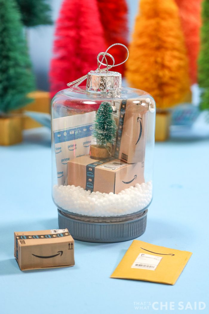 Two snow globe jar ornaments. Inside has fake snow and miniature Amazon boxes and envelopes