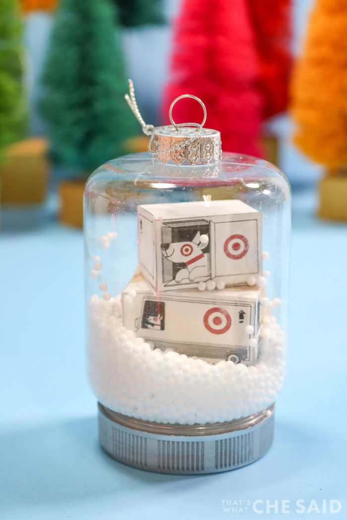 Two snow globe jar ornaments. One has miniature target boxes and fake snow