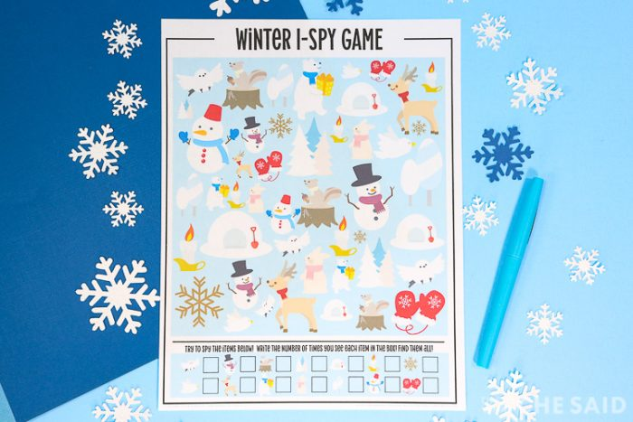 Blue background with snowflakes and the printed printable wiith a blue pen in horizontal format