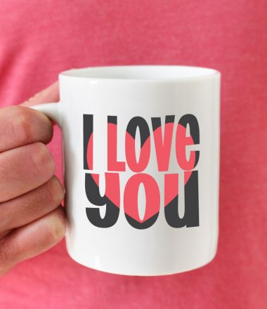 Man in pink shirt holding coffee mug with I love you block out design