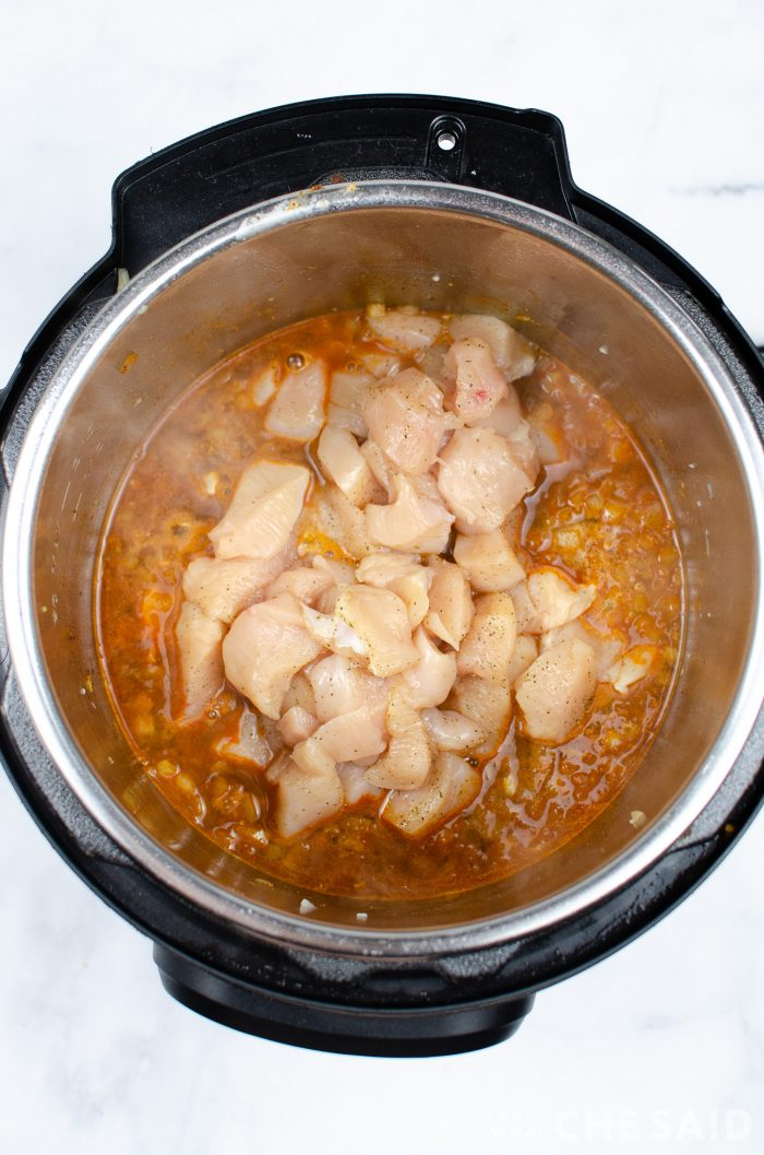 Cubed Chicken added to instant pot inner pot for chicken burrito bowl recipe