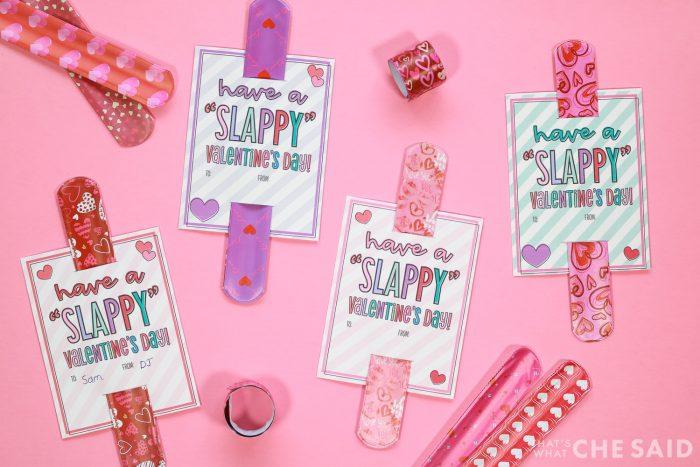 Slap Bracelet Valentines assembled on a pink background with extra slap bracelets surrounding them